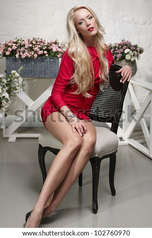Art portrait of fashion model posing in the chair - stock photo