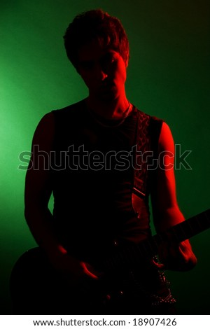 art portrait of guitarist over green background - stock photo