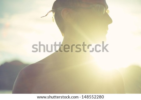 Art portrait of young man in sport glasses at sea - stock photo