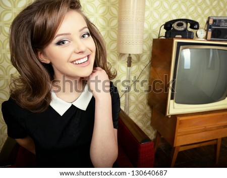 art portrait of young smiling ecstatic woman looking out at camera in room with vintage wallpaper and interior, retro stylization 60-70s, toned