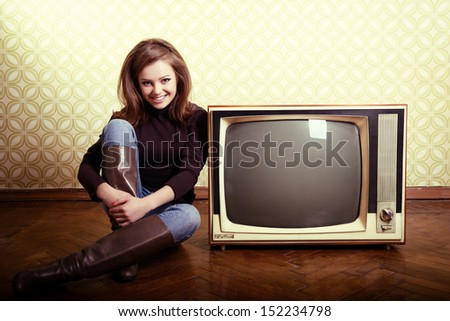 art portrait of young smiling ecstatic woman sitting near retro tv set in room with vintage wallpaper, stylization 60-70s, toned - stock photo
