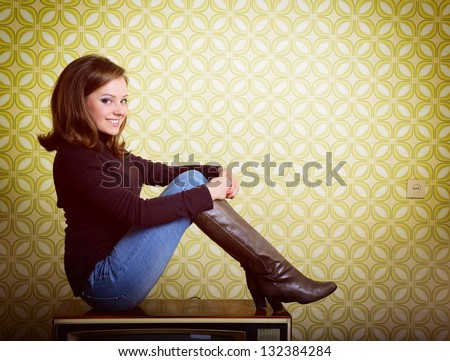art portrait of young smiling ecstatic woman sitting on tv set and looking out at camera in room with vintage wallpaper and interior, retro stylization 60-70s, toned