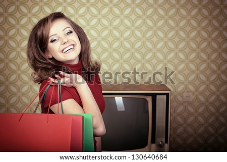 art portrait of young smiling woman and holding shopping sale bags in room with vintage wallpaper, retro stylization 60-70s, toned - stock photo