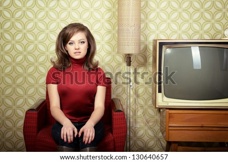 art portrait of young woman sitting on chair and looking at camera in room with vintage wallpaper and interior, retro stylization 60-70s, toned