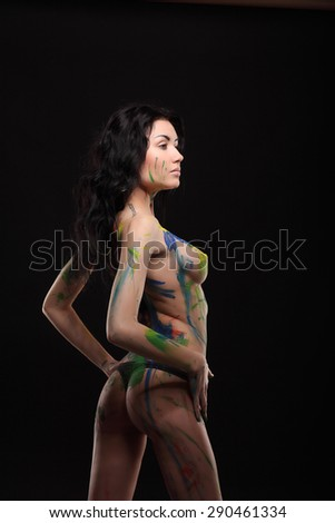 Art project: beautiful woman painted with many vivid colors studio - stock photo