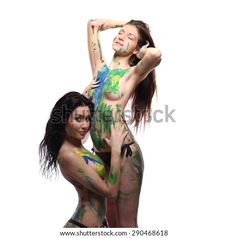 Art project:  two lesbian beautiful woman painted with many vivid colors studio - stock photo
