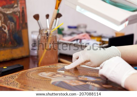 Art restorer working on the old icon with spatula at restoration workshop - stock photo