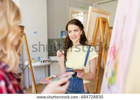 art school, creativity and people concept - women artists or student girls with easel, palettes and paint brush painting at studio