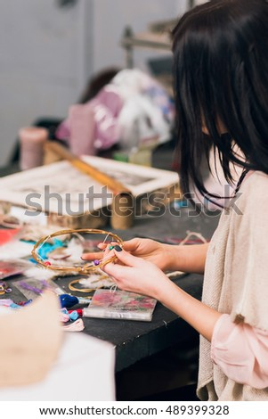 Art studio with creating dream catcher artisan. Unrecognizable woman weaving wooden circles for house decoration. Creativity, handicraft, hobby concept