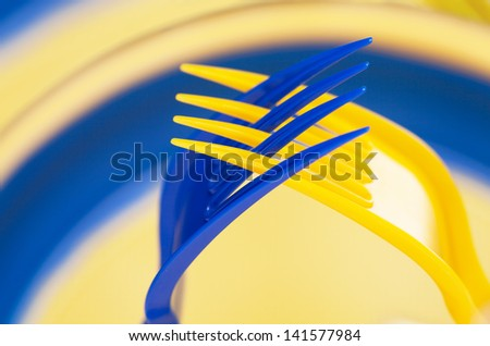 Art, Two plastic forks, blue and yellow, put together in a gesture of prayer - stock photo