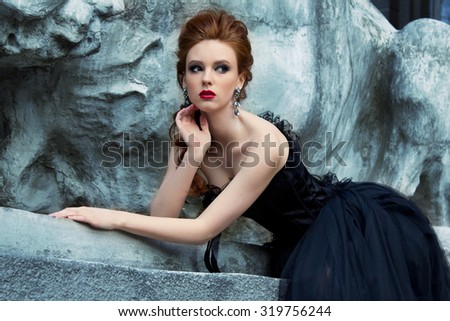 Art work Gothic fashion: a beautiful young girl in black dress and headwear sitting near castle. Toned and noise added. - stock photo