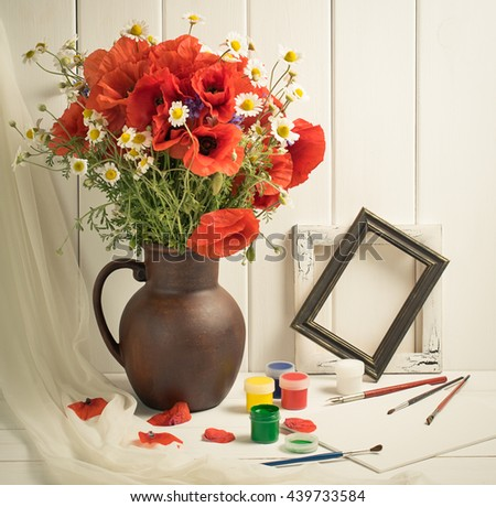 Art workshop with  Artistic equipment and composition still life poppies with daisy in clay jug and tulle fabric. Painting studio with canvas, paints, frames and paint brushes in the interior. - stock photo