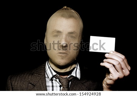 Artful dodgy salesman with business card and a stocking mask going about his nefarious business of deception and fraud - stock photo