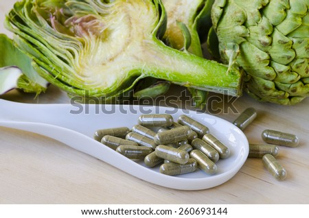 Artichoke leaf extract capsules. Dietary supplements. Selective focus. Taken in daylight. - stock photo