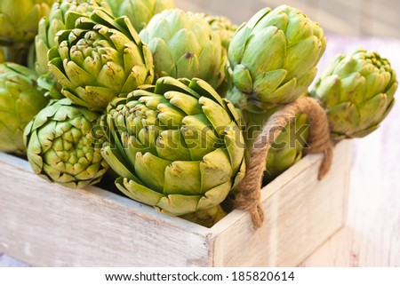 Artichokes in a wooden box. Close-up.  - stock photo