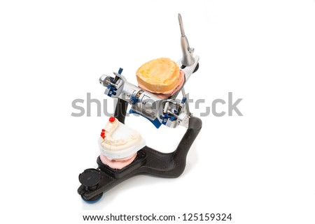 Articulator in a dental lab with mold or artificial denture - stock photo