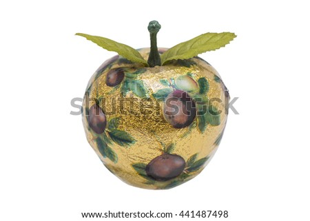 Artificial apple made of wood with gold paper and pattern, with green plastic leaves on isolated white background - stock photo
