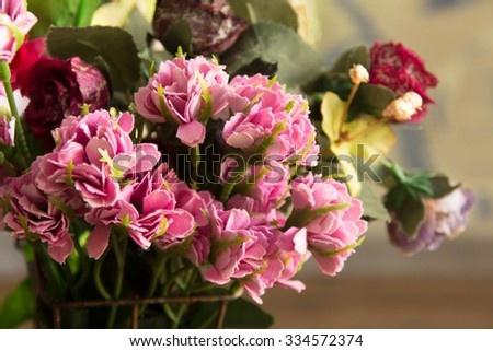Artificial beautiful flowers on wooden background,still life