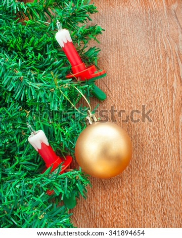 Artificial Christmas tree, electric candles and golden ball on the background texture of oak - stock photo