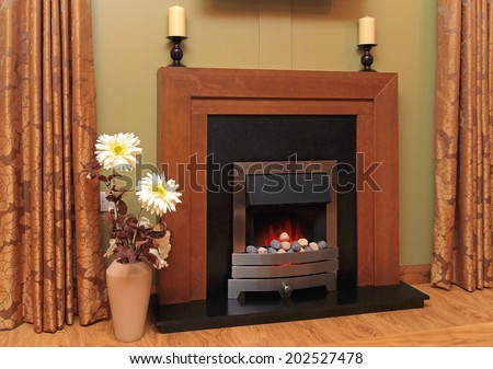Artificial fire in fireplace with lava rocks