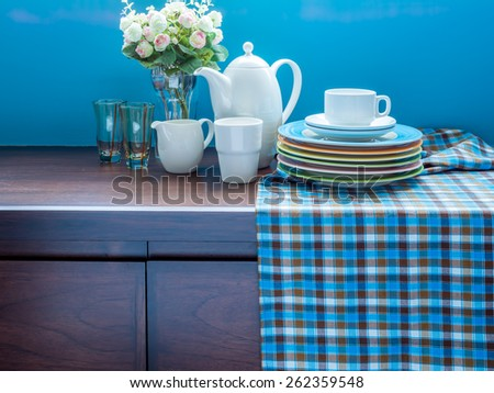 Artificial flower vase, teapot and dishware on wooden cupboard/ interior still-life - stock photo