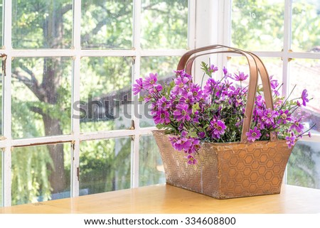 Artificial flowerpot near the glass window and have green tree on a background. - stock photo