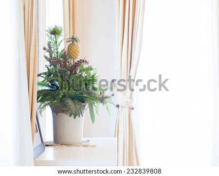Artificial flowers bouquet on window sill frame with curtains - stock photo