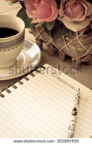 Artificial flowers, coffee cup and notebook in age photo style