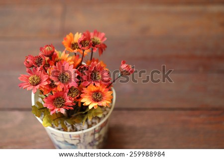 Artificial flowers in small pot on wooden table with empty space for background. - stock photo