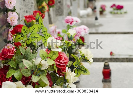 Artificial flowers on the tomb  at the cemetery with burning red candle - stock photo