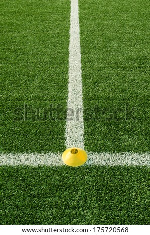 Artificial green turf texture background with white line marks and yellow plastic  cone