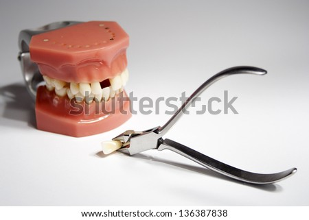 Artificial jaw and dentistry tongs - stock photo