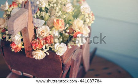 Artificial rose bouquet in wooden flowerpot on wood table & background, selective focus, vintage filter