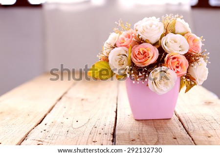 Artificial roses blossom on wood background - stock photo