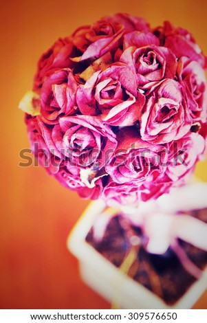 Artificial roses bouquet in small pot, vintage style image. - stock photo