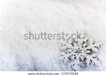 Artificial snowflake on snow background
