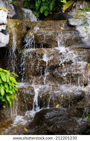 Artificial tropical garden waterfall - stock photo