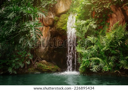 Artificial tropical garden waterfall - stock photo