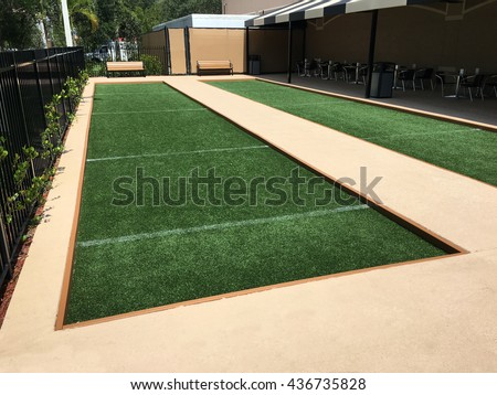 Artificial turf bocce ball courts at the park with cafe style seating.