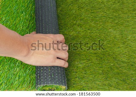Artificial turf green grass roll replace with hand - stock photo
