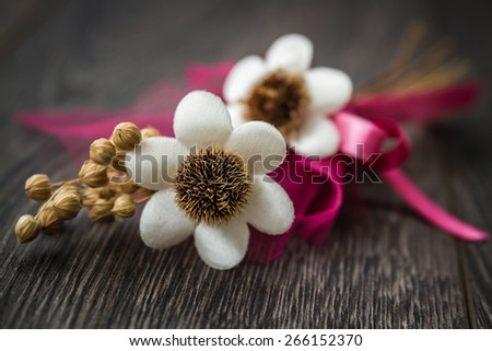 Artificial white, pink flower bouquet on dark brown wooden table - stock photo