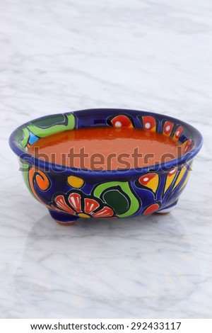 Artisan hot taco sauce in vintage talavera bowl, with a delicious fresh hot flavor,  on vintage carrara marble table.