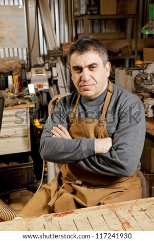 Artisan looking to camera sitting at workbench arms folded - stock photo