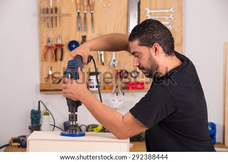 Artisan using a hole saw while crafting a cajon flamenco percussion instrument - stock photo