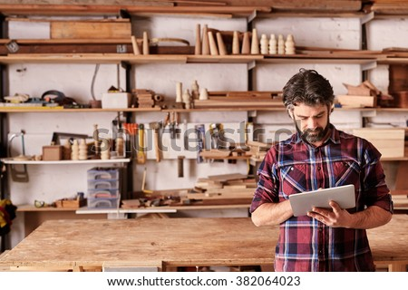 Artisan woodwork studio with shelving holding pieces of wood, with a carpenter standing in his workshop using a digital tablet