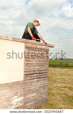 artisan working on a wooden construction for a summerhouse