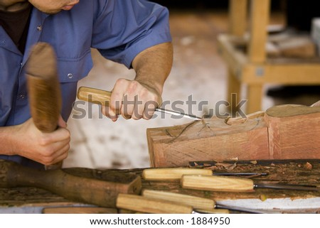 artisan working with mallet and chisel - stock photo