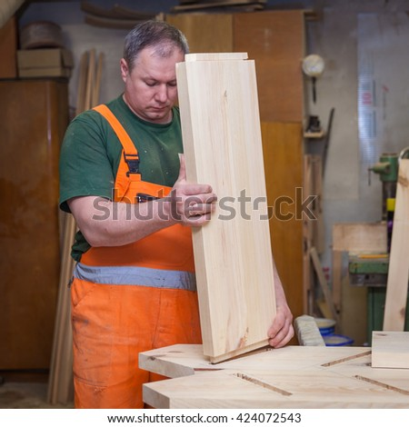 artisans in woodwork trying plate for use in making wooden furniture