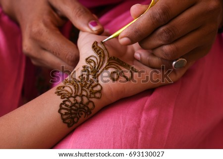 Artist Applying Beautiful Henna Tattoo Arabic Design To A Womans Or Indian Brides Hands At City