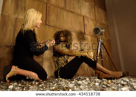 Artist applying makeup to model at photo shoot on floor in bright gold studio - stock photo